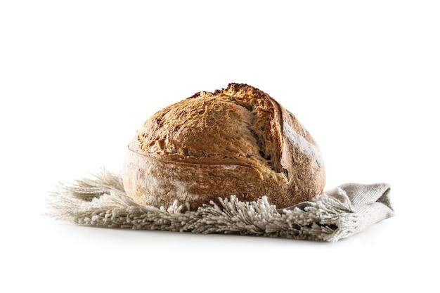 Изолированные свежеиспеченный хрустящий буханка дрожжевого хлеба, лежащая на льняной посуде.