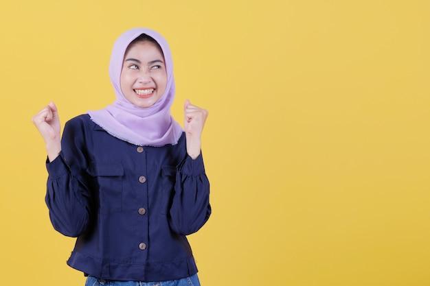 Изолированные от красивых женщин, которые преуспевают в ношении хиджабов, поднимающих кулаки, празднующих победу, очень счастливых и счастливых на желтом фоне