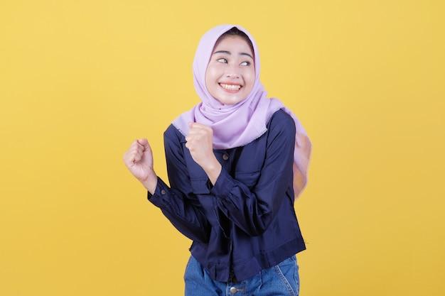 ヒジャーブを身に着け、握りこぶしを上げ、勝利を祝い、黄色の背景で非常に幸せで幸せになることで成功する美しい女性から隔離されています