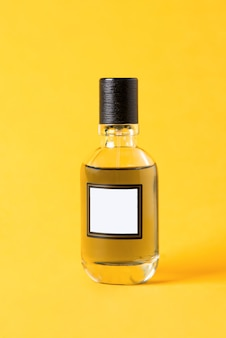 Isolated glass bottle of perfume lies on the yellow background. minimalistic abstract mock up. women men unisex fragrance.