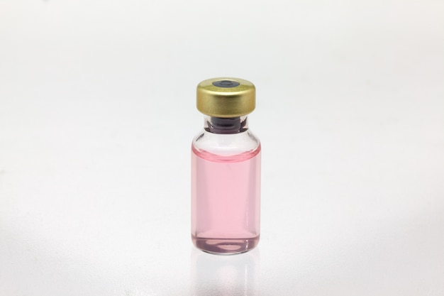 Isolated glass vaccine bottle with colored liquid very close high magnification mockup