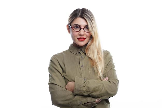 Isolato splendida attraente giovane donna che indossa occhiali alla moda, rossetto rosso e sciolti capelli colorati su un lato guardando con un sorriso fiducioso, tenendo le braccia conserte