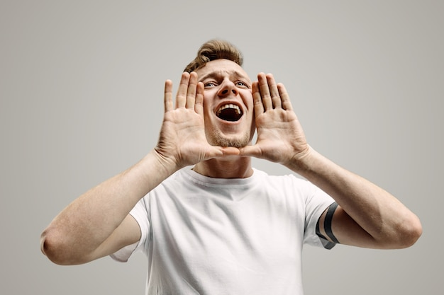 Isolated on gray young casual man shouting
