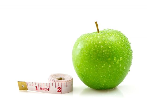 Изолированное зеленое яблоко с измеряя лентой на белизне, концепция здоровой и диета.