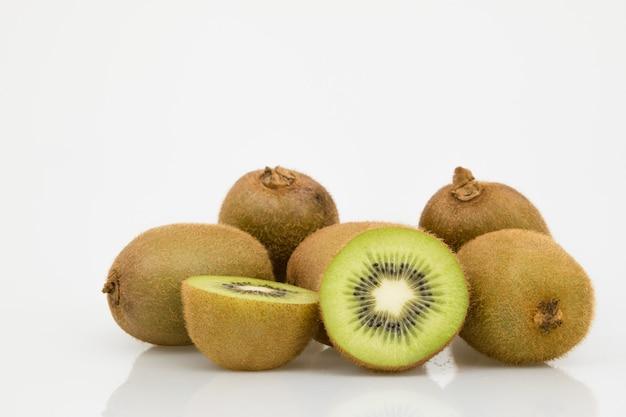 Isolated half cut kiwi fruits on white.