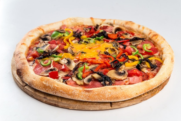 Isolated ham and vegetables pizza with mushrooms on a wooden board