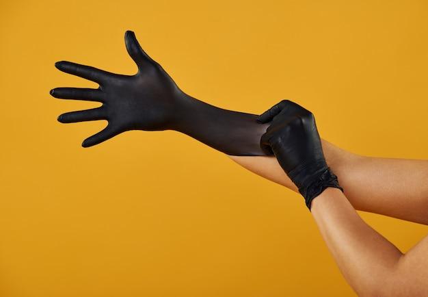 黄色の背景の孤立した手は、黒いラテックス医療用手袋を着用します。