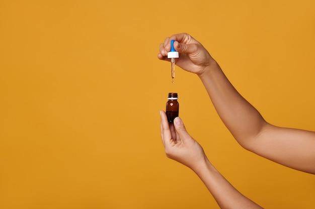 Изолированные руки с бутылкой масла, выжимая каплю масла из пипетки.