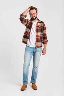 ジーンズに身を包んだ流行に敏感な衣装で孤立したハンサムなひげを生やした男