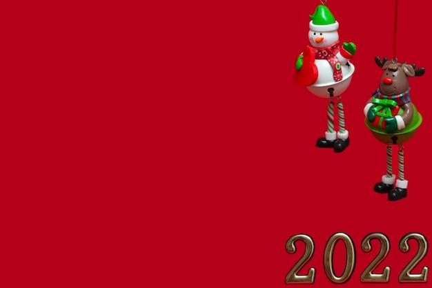 빨간색 배경에 크리스마스 장난감을 매달아 격리: 눈사람과 눈 사슴. 새해 인사말 카드, 초대장 및 포장에 대한 개념. 배너.