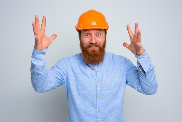 Isolated happy architect with beard and orange helmet