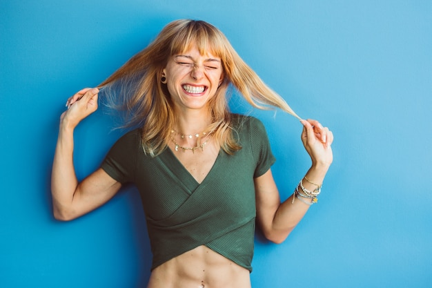 Isolated happy funny woman having fun over a blue background. portrait of a positive joyful girl