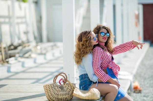 Две привлекательные девушки, веселые лучшие друзья веселятся на пляжной вечеринке. носить летний наряд, шорты и футболки, весело модно выглядя с красивыми волнистыми волосами. isolated.hat и солнцезащитные очки