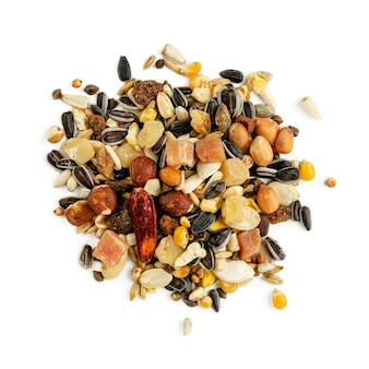 Isolated heap of parrot fodder of dried fruits, nuts and seed mix.