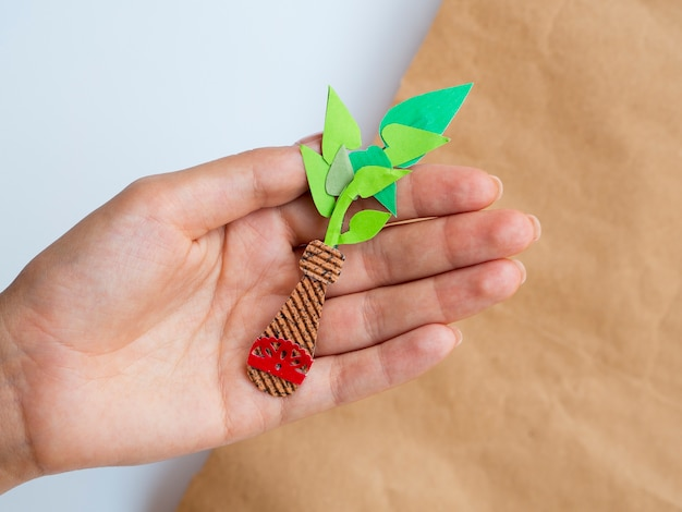 Isolated homemade paper plant held in hand