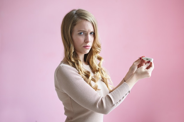 Isolated horizontal picture of frustrated upset young european lady with blonde wavy hairstyle frowning, feeling worried and scared, having positive pregnancy test, not sure about her decision.