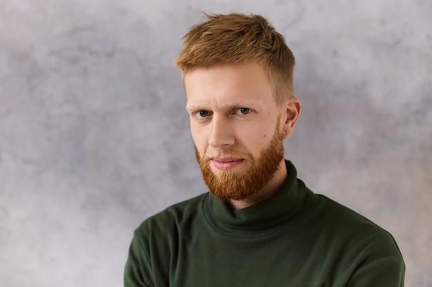 Immagine isolata di attraente dai capelli rossi barbuto giovane maschio caucasico vestito in abiti eleganti ed eleganti fissando con sguardo concentrato intenso. espressioni facciali umane e atteggiamento