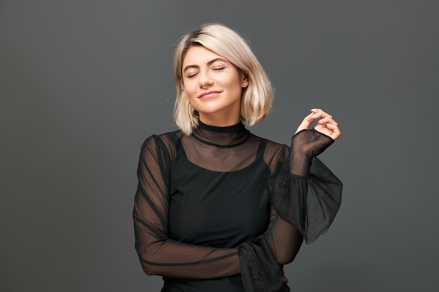 Isolated image of beautiful stylish young female wearing stylish evening dress and nose ring posing  with eyes closed, smiling, enjoying pleasant festive music. winter and holidays concept
