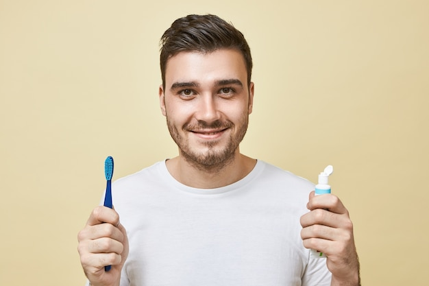 Isolated image of confident cheerful young brunette guy with bristle holding brush and tube of toothpaste, brushing teeth right after awakening. hygiene, morning routine and teeth whitening concept