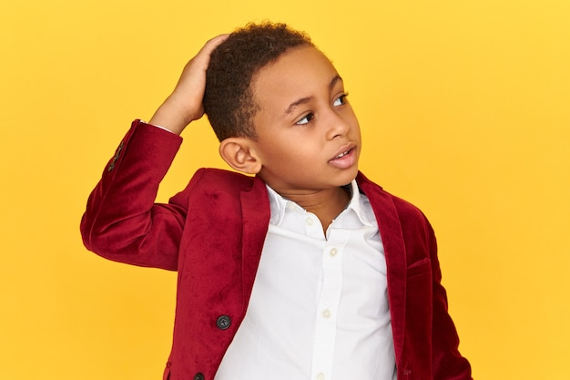 Isolated image of cute confused afro american schoolboy looking up with puzzled perplexed facial expression scratching head, forgot to do homework, being embarrassed.
