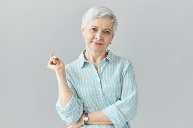 Isolated image of elegant fashionable middle aged european woman on retirement posing  wearing stylish striped blue shirt and wrist watch, having good day, smiling  happily