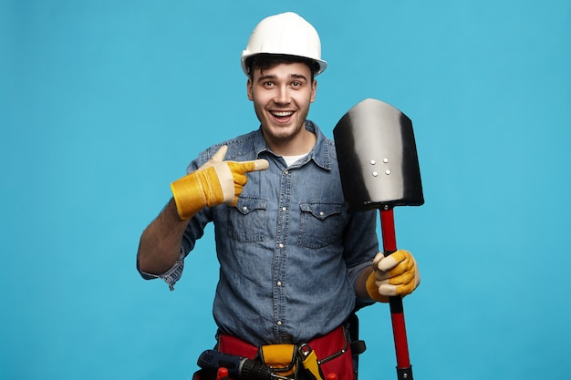 Isolated image of emotional cheerful young maintenance worker in overalls looking at camera