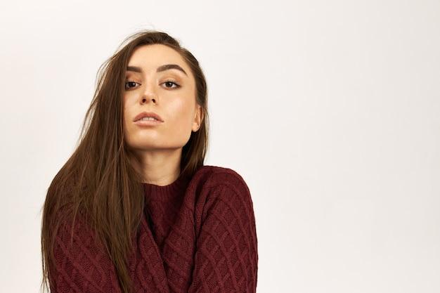 Immagine isolata di bella bella giovane donna con lunghi capelli borwn in fase di riscaldamento in maglione lavorato a maglia in posa contro il bianco della parete di studio di sfondo con spazio di copia