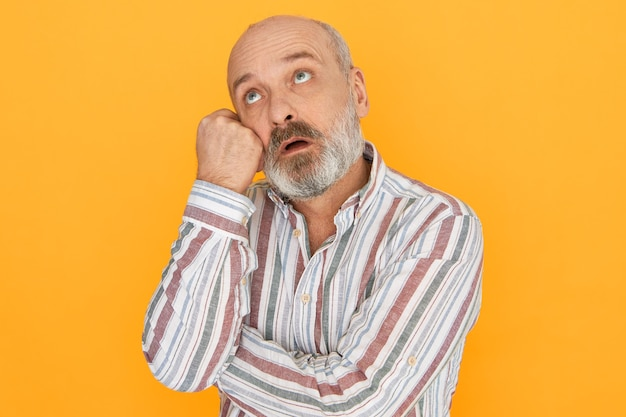 Isolated image of handsome pensive bearded caucasian male pensioner with puzzled confused expression having memory problems, holding hand on face and looking up, trying to remember something.