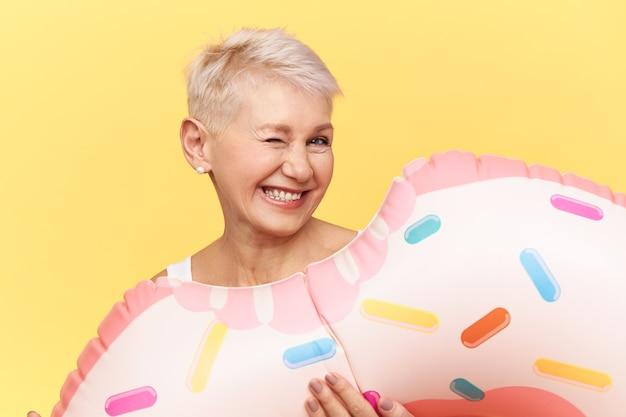 Immagine isolata di felice divertente donna di mezza età con corti capelli biondi scherzare sulla spiaggia in riva al mare, in posa su sfondo giallo con cerchio di nuoto