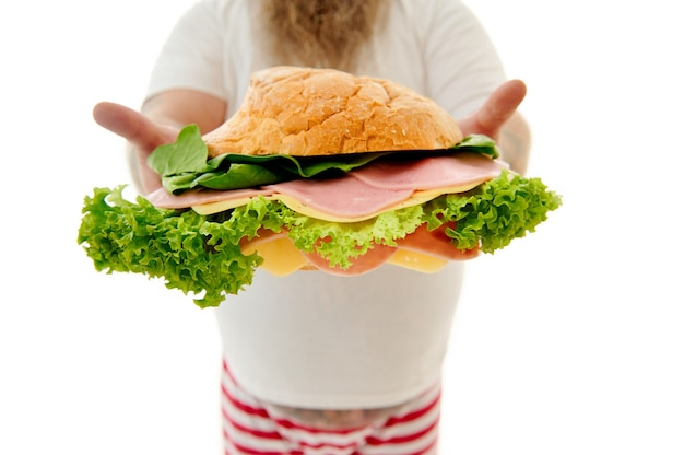 Isolated image of huge burger with slices of sausages, cheese and lettuce leaves