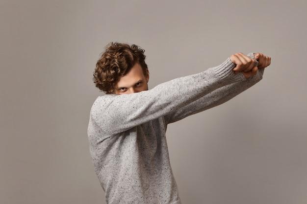 Immagine isolata del misterioso bel ragazzo con voluminosa acconciatura riccia alla moda che balla mantenendo il viso vicino alla spalla e le braccia tese,