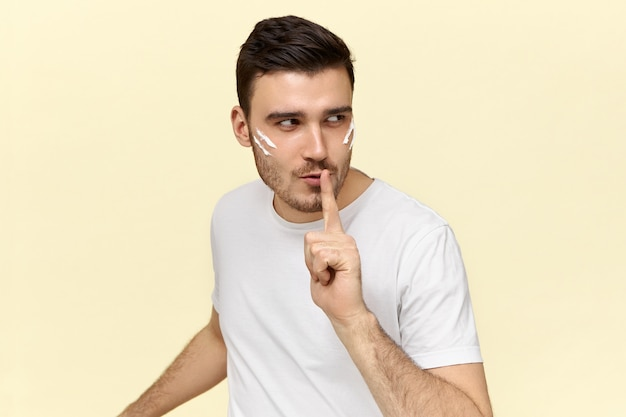 Isolated image of mysterious young male dressed in casual white t-shirt keeping index finger on lips, asking to be quiet and not tell his secret to other people.