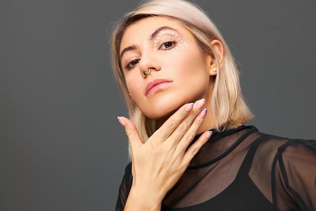 얼굴 피어싱과 세련된 메이크업으로 매력적인 유행 젊은 여성 모델의 고립 된 이미지는 트렌디 한 검은 색 투명 블라우스를 입고 포즈를 취합니다. 여성 스타일, 패션 및 매력적인 개념
