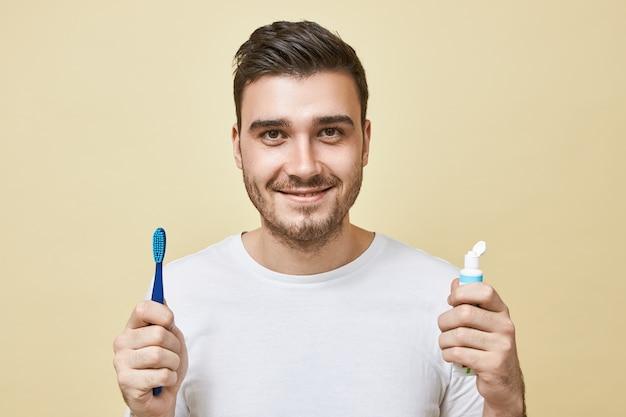 깨어 난 직후 양치질 브러시와 치약의 튜브를 들고 강모와 자신감 쾌활 한 젊은 갈색 머리 남자의 고립 된 이미지. 위생, 아침 루틴 및 치아 미백 개념