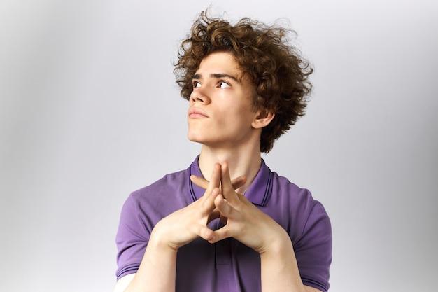 Immagine isolata di pensieroso giovane uomo caucasico con voluminosa pettinatura alzando lo sguardo stringendo le mani insieme, pensando o sognando, facendo piani per il futuro. linguaggio del corpo ed espressioni facciali umane