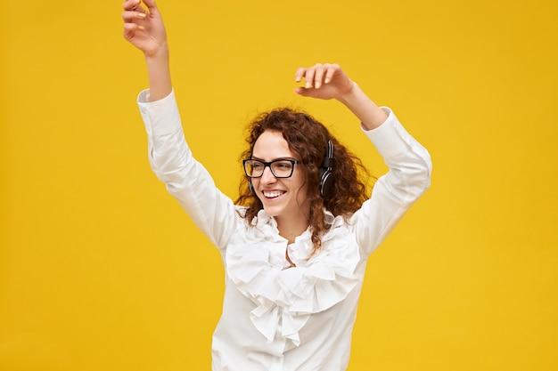 Immagine isolata di giovane donna emotiva positiva con capelli scuri ricci in posa al muro giallo con le mani in aria, ballare, ascoltare musica in cuffia, sorridere eccitato, con gli occhiali