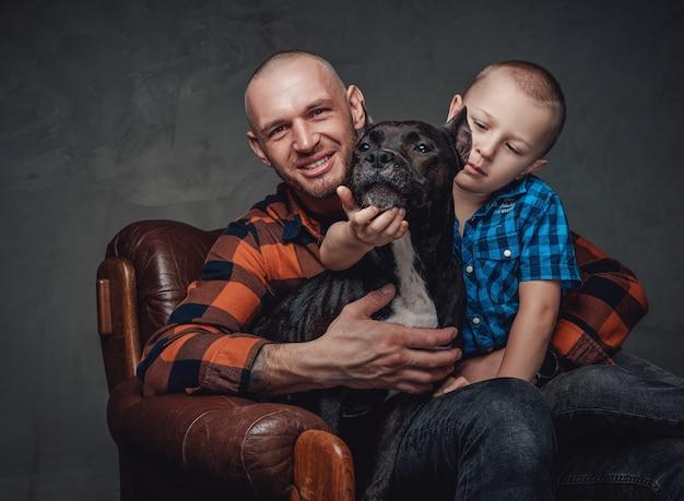 Изолированные в темном фоне молодая семья взрослого отца с сыном и собакой.