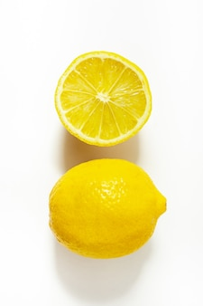 Изолированные лимон и половина лимона на белом фоне (жесткий свет) вид сверху