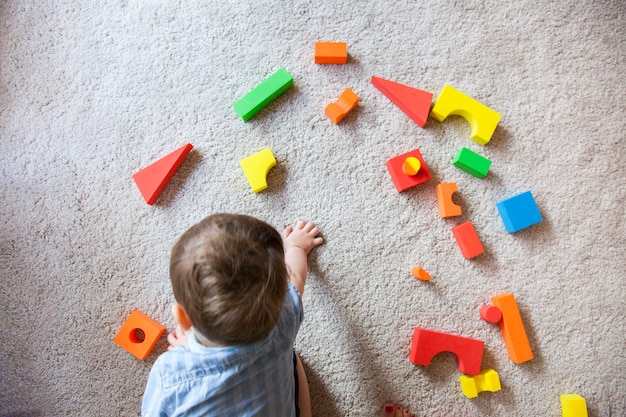 Isolated little boy learning how to play with shapes and colors with educational game.