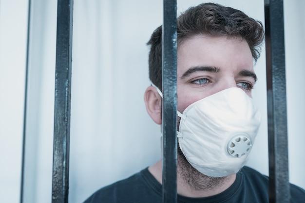 Изолированный человек при медицинская маска идя через карантин дома из-за сигнала тревоги здоровья.