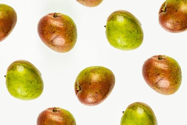 孤立したマンゴーパターンまたは白い背景の壁紙。上から撮影した新鮮な完熟マンゴーフルーツの夏のコンセプト