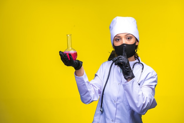 Isolated nurse in hand and face mask holds chemical flask and makes point to danger