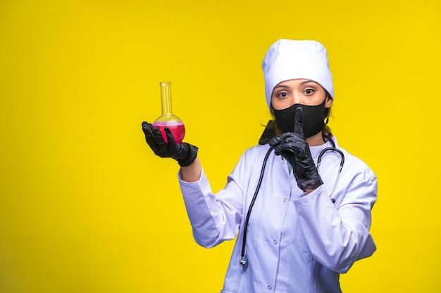 Изолированная медсестра в руке и в маске держит фляжку с химикатом и указывает на опасность