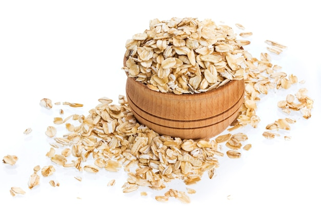 Isolated oatmeal. oat flakes in wooden bowl on white surface