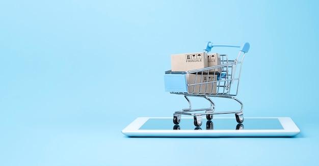 Изолированные из транспортировочных бумажных коробок внутри синей тележки для покупок на планшете, изолированном на синем