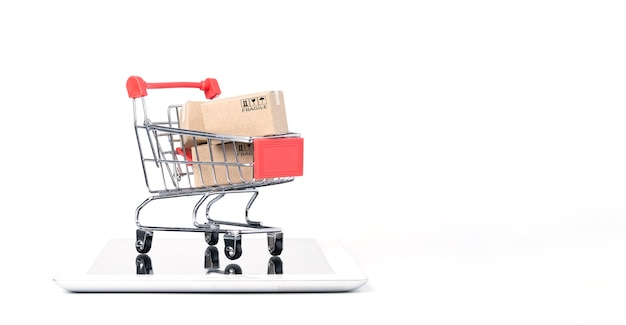 Изолированный коробки перевозкы груза бумажные внутри красной тележки тележки для покупок на таблетке с белой предпосылкой и космосом экземпляра, интернет-магазинами и концепцией электронной коммерции.