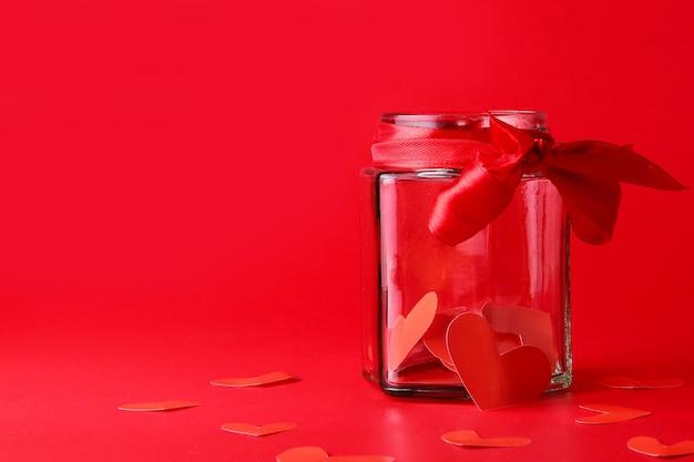 Изолированные на красном фоне красная бумага в форме сердца находится внутри банки с красной лентой
