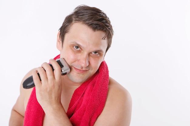 白い背景で隔離:無精ひげを剃る男。男はひげを電気かみそりで掃除します。バスルームでの朝のトリートメント。彼女の首に赤いタオル。コピースペース