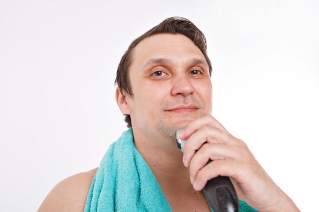 白い背景で隔離:無精ひげを剃る男。男はひげを電気かみそりで掃除します。