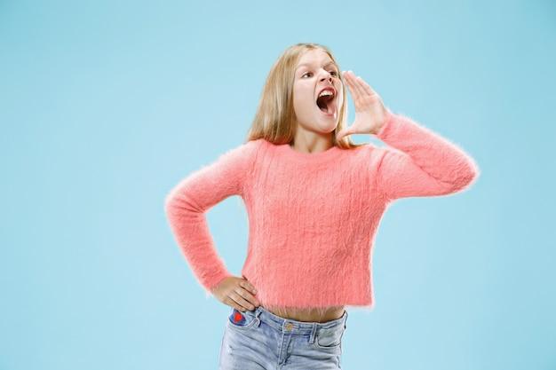 Изолированные на синем молодая случайная девушка кричит